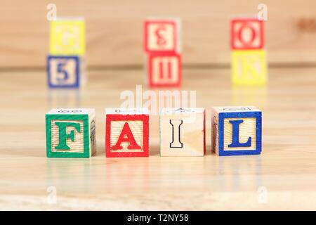 Wooden blocks with letters. Children educational toy concept - failing in school. - Stock Photo