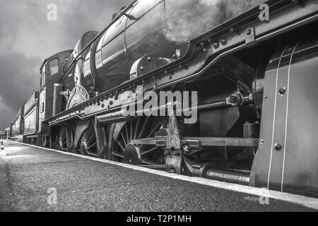 Black and white, moody, close-up side view of a vintage UK steam train awaiting departure alongside station platform, taken from a very low angle. - Stock Photo