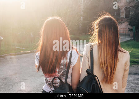 Two skinny young women in the sunset. The view from the back. - Stock Photo