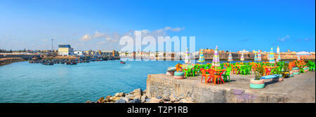 Panoramic cityscape with colorful street cafe on quay of fishing port at Essaouira. Morocco, North Africa - Stock Photo