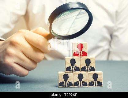 Businessman holds a magnifying glass over the cubes with the image of employees. Staff recruitment. Select a person in the team. Find a talented emplo - Stock Photo