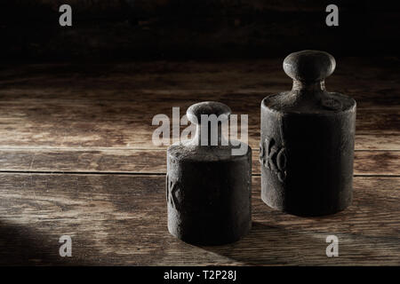 Two old antique metal kilogram weights placed in the corner on rustic wooden table for measuring and counterbalance on a scale - Stock Photo
