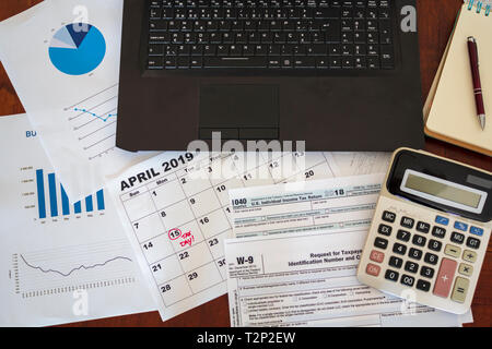 Top view of desk with laptop, calculator, tax forms, graphs and calendar. Tax season concept - Stock Photo