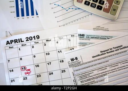 Top view of desk with calculator, tax forms, graphs and calendar sheet with tax date marked - Stock Photo