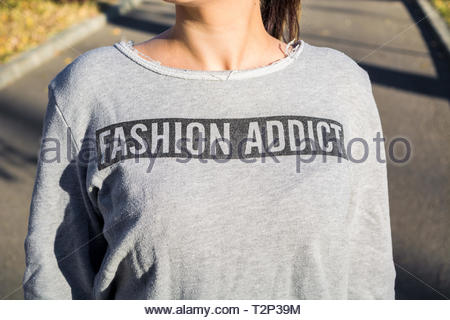 Young girl with gray loose sweatshirt that has 'Fashion Addict' written on it. Concept of fashion, shopping, consumers. Pitesti, Romania ,Europe. - Stock Photo