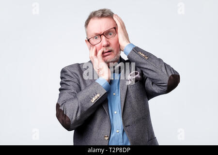 Frustrated mature man holding hand on his head, having forgetful look or teeth pain. Negative facial emotion. - Stock Photo