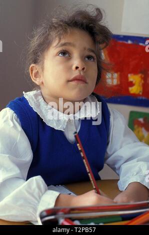 contemplative little girl in school classroom - Stock Photo