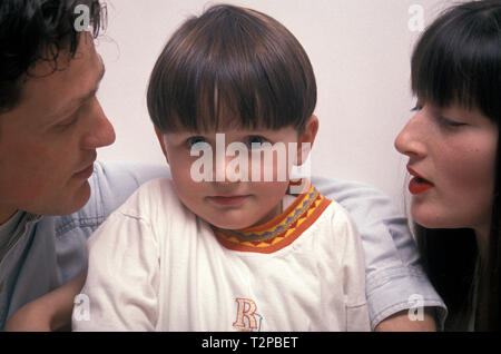 cheeky little boy between his two parents - Stock Photo