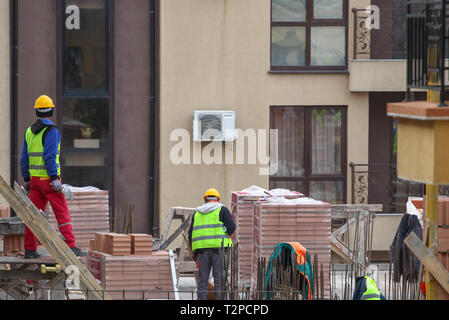Pomorie, Bulgaria - March 14, 2019: Bricklayer Preparing Laying Bricks On Wall. - Stock Photo