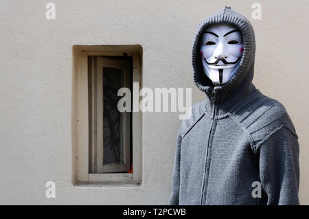Velvary, CZECH REPUBLIC – February 27, 2019: An unidentified man is wearing the Vendetta mask and standing in front of a wall - Stock Photo