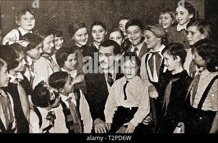 A 1940's portrait of Russian children's author M. Sergei Mikhalkov (aka  Sergey Vladimirovich Konchalovsky ) - 1913-2009 -with a group of Moscow,children. He composed the lyrics to the |Soviet National Anthem and wrote a number of satirical plays and comedy scripts and was awarded a number of  honours and awards - Stock Photo