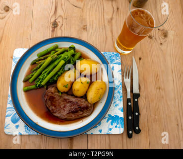 A fried Aberdeen Angus rump beef steak served with new potatoes, tenderloin broccoli and asparagus and gravy on a blue edged plate on a wooden table - Stock Photo