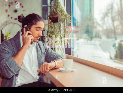 Portrait of frustrated, annoyed attractive man with modern hairdo having call speaking by smart phone looking at watch on wrist worried. Closeup of a  - Stock Photo