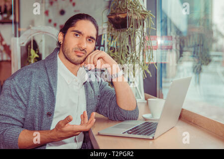 Man looking at you camera frustrated hand gesture in front of the computer. Closeup portrait of a handsome guy wearing white shirt, gray blouse sittin - Stock Photo