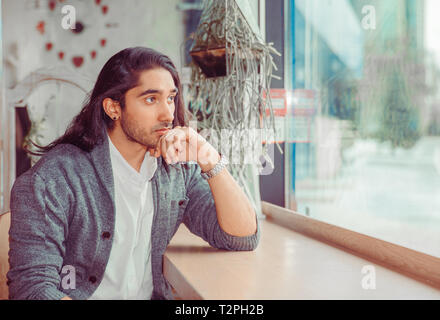Thoughtful young man in the living room. Closeup portrait of handsome guy wearing formal white shirt, gray blouse sitting near window at table in livi - Stock Photo