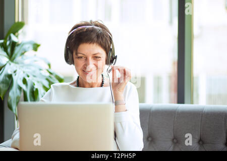 Modern mature woman wearing, holding headset sitting at table in front of computer, laptop looking at it, smiling happily. Positive freelancer, custom - Stock Photo