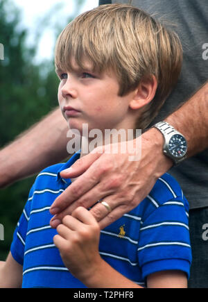 A boy holds his father's hand during a ceremony commemorating the fifth anniversary of Hurricane Katrina, Aug. 29, 2010, in Gulfport, Mississippi. - Stock Photo
