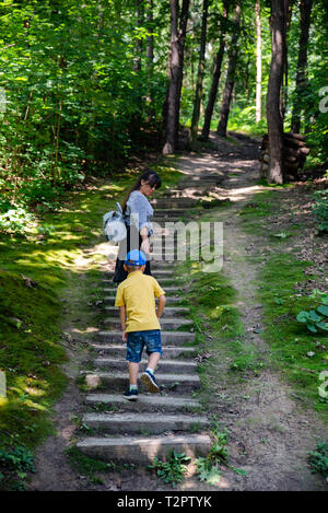young mother with little kid climbing up by old stairs in forest. summer time - Stock Photo