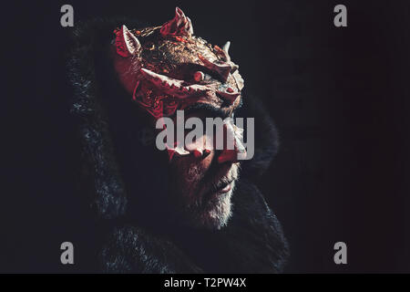 Alien, demon, sorcerer makeup. Horror and fantasy concept. Man with thorns or warts. Demon on black background, copy space. Senior man with white bear - Stock Photo