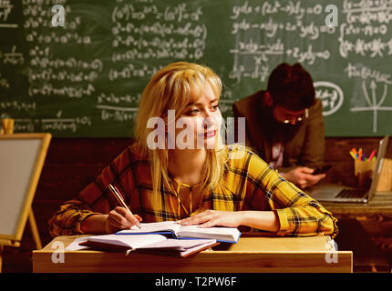 Tutor will have to re-evaluate the students objectives. Trained professional who teaches group of students. Students sitting together at table - Stock Photo