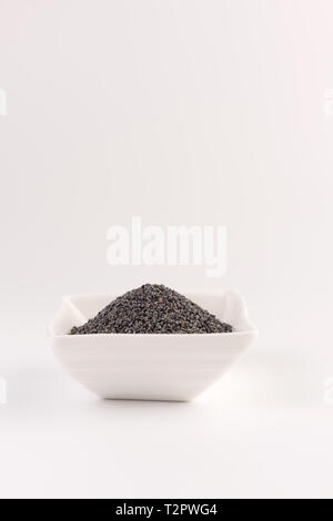 Poppy seeds in a ceramic plate isolated on white background. Selective focus - Stock Photo