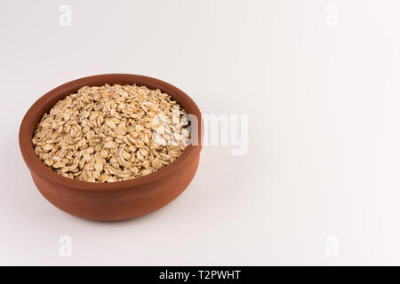 Dry rolled oatmeal in bowl isolated on white background. - Stock Photo