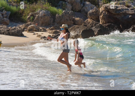 happy family playing together on the beach - Stock Photo