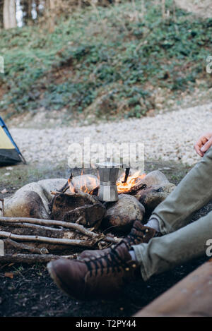 Cropped outdoor image of young man explorer sitting near to bonfire preparing hot beverage in mountains. Concept adventure active vacations. Summer ca