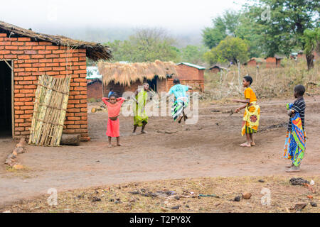girls playing with a skipping rope in a village in Malawi - Stock Photo