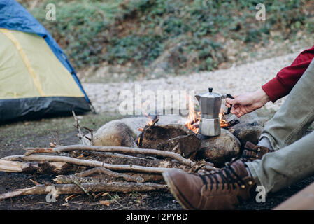 Cropped outdoor image of young man explorer preparing hot beverage in mountains. Traveler man sitting near to bonfire on background camping tent, cook