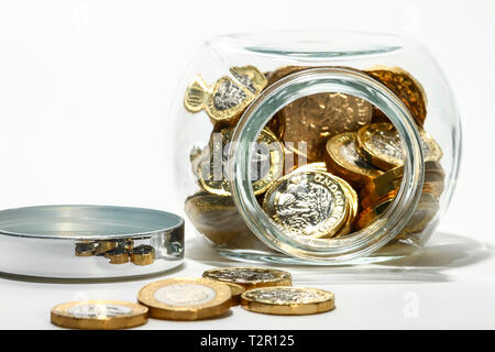 Glass jar full of pound coins isolated on a white background - Stock Photo