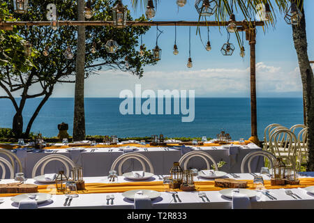 Set white tables for wedding dinner decorated in Mediterranean style. View of the ocean. Concept of a tropical destination wedding. - Stock Photo