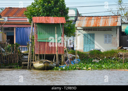 Can Tho, Vietnam - December 31st 2017. A man pushes his rowing boat through the vegetation to the shore at the back of his house on a waterway - Stock Photo