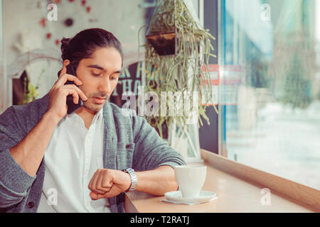 Portrait of responsible attractive man with modern hairdo having important call speaking by smart phone looking at luxury watch on wrist. Closeup of a - Stock Photo
