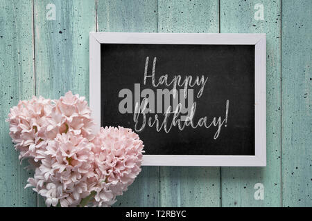 Springtime flat lay with pink hyacinth flowers and blackboard with text 'Happy Birthday' on mint rustic wooden planks. Flat lay with lettering greetin - Stock Photo