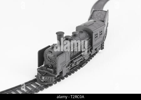 Black painted toy steam engine model and track. Metaphor On the Right Track, gravy train, old railroads, rail network, toy train set, career track. - Stock Photo