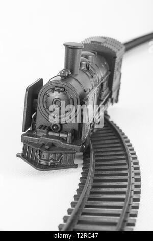 Black painted toy steam engine model. Metaphor off track, financial crash, knocked off course, train accident, end of gravy train, Oops, train wreck - Stock Photo