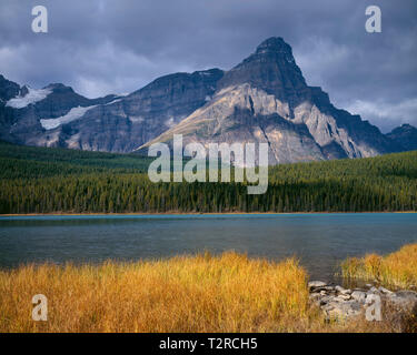 Canada, Alberta, Banff National Park, Upper Waterfowl Lake and Mt. Chephren with dark clouds. - Stock Photo