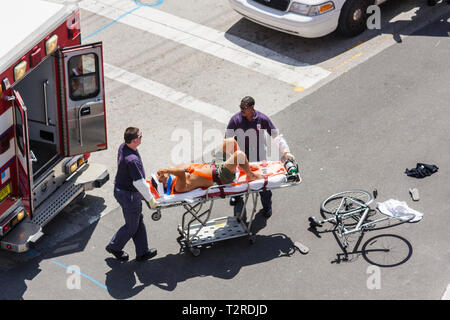 Miami Beach Florida intersection accident cyclist bicycle injury injured man fire rescue paramedic emergency medical service str - Stock Photo