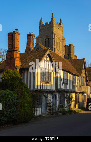 View of a row of medieval half timbered houses in the village of Stoke By Nayland with the local church tower rising behind them, Suffolk, England, UK - Stock Photo