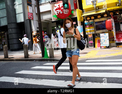 Pictured is a girl walking the streets of Tokyo Japan - Stock Photo