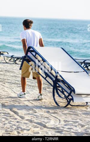 Miami Beach Florida Atlantic Ocean sand shore public beach rental lounge chair man attendant job working guest service carry dra - Stock Photo