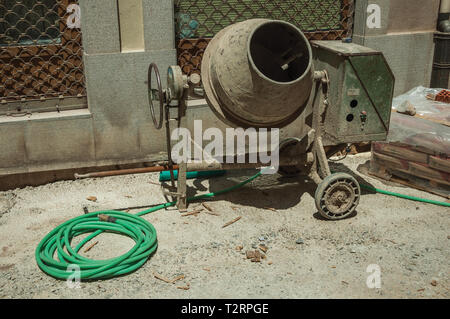 Old cement mixer with hose and cement bags in a construction site at Avila. With an imposing wall around the gothic city center in Spain. - Stock Photo