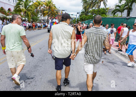 Miami Beach Florida South Beach Ocean Drive Lummus Park Gay Pride Festival expo homosexual LGBT man men couple walking hold ha - Stock Photo