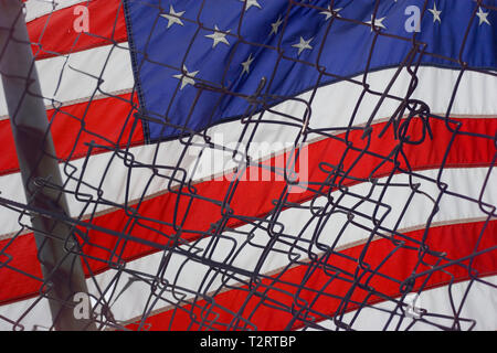 American Flag behind a rusted, broken fence - Stock Photo