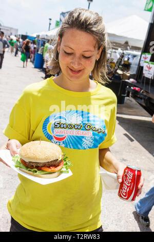 Miami Florida Bayfront Park Miami Goin' Green eco-friendly green event community fair woman food hamburger vendor tent Coca Cola - Stock Photo