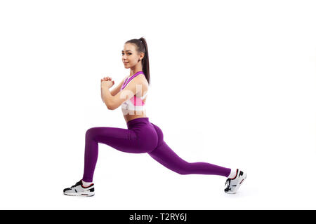 A young  woman coach in a sporty  short top and gym leggings makes lunges  by the feet forward, hands are held out to the side   on a  white isolated  - Stock Photo