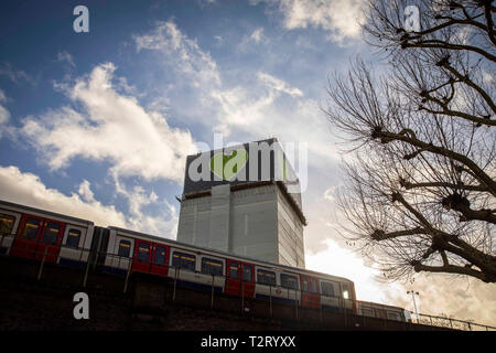 The top of Grenfell Tower pictured with a tube train in the foreground in December 2018. - Stock Photo