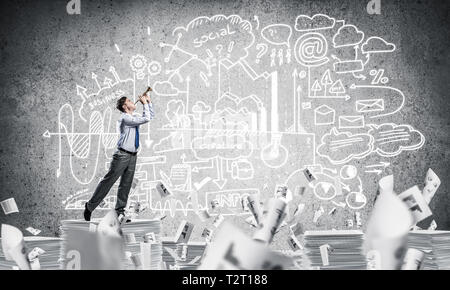 Businessman playing fife while standing on pile of documents among flying papers with business-analytical information on background. Mixed media. - Stock Photo