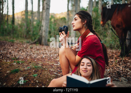Young smiling couple of women wearing dresses reading a book and taking photos with old camera in the forest with their horse. - Stock Photo
